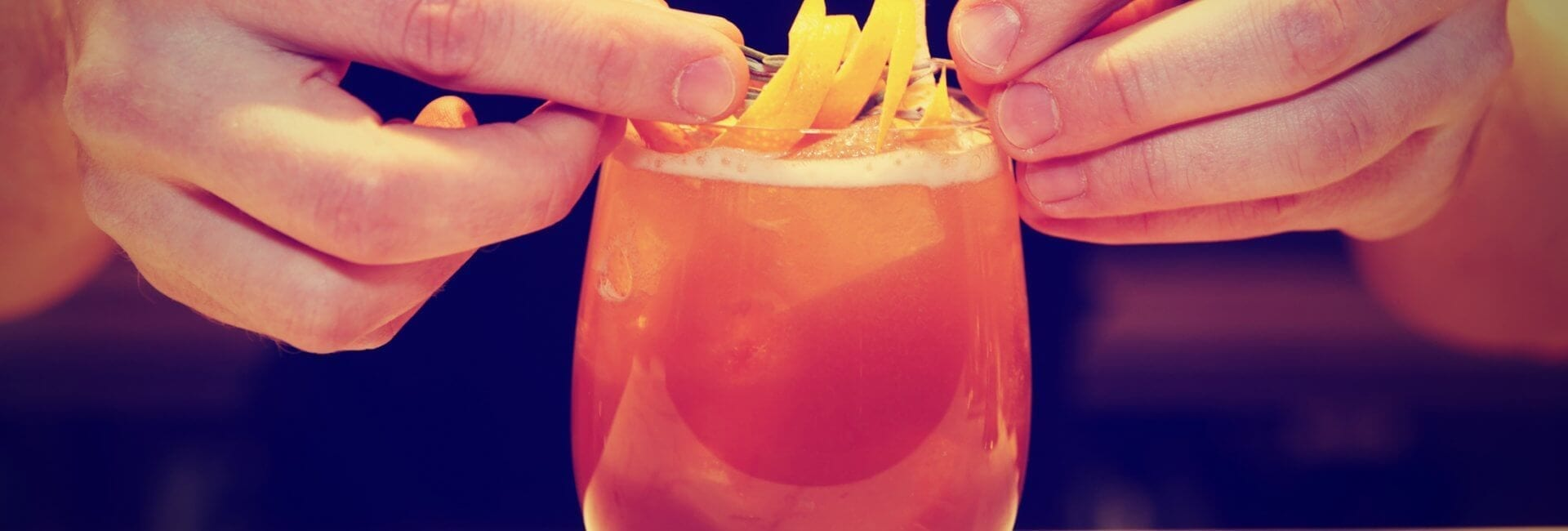 color photo of a close up of two hands placing lemon peel garnish on top of a red cocktail