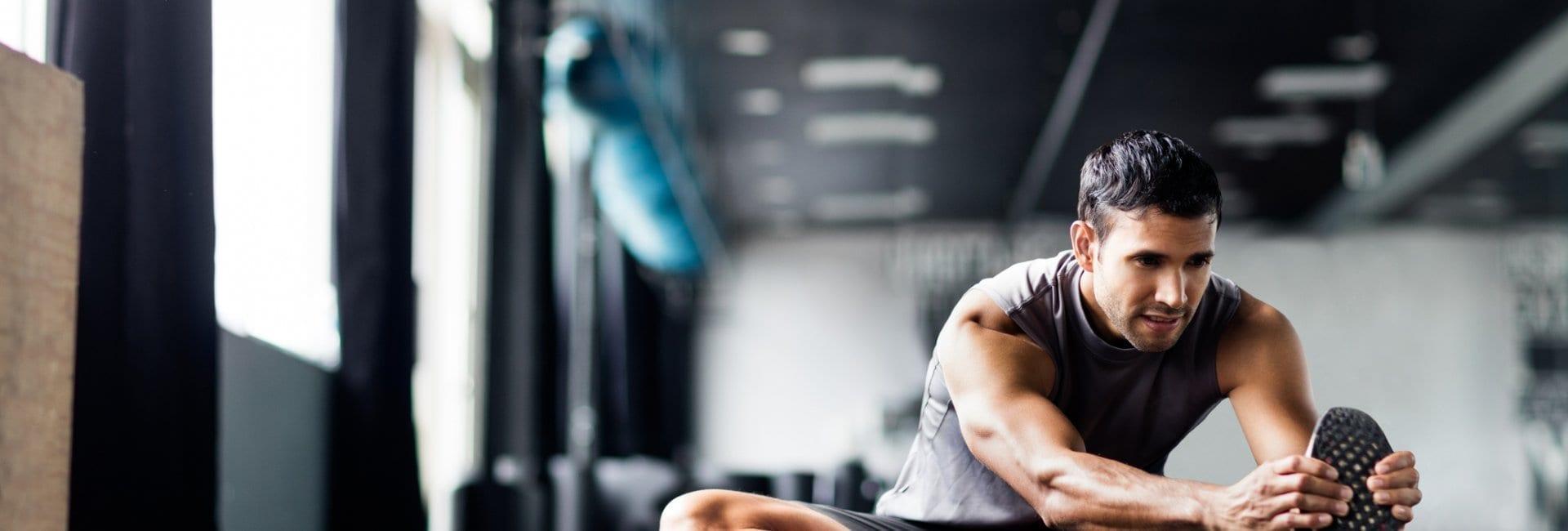 Man stretching in gym